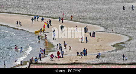 Different people doing different things - a Lowry-like scene on the sands of Scarborough's South Bay beach. - Stock Image