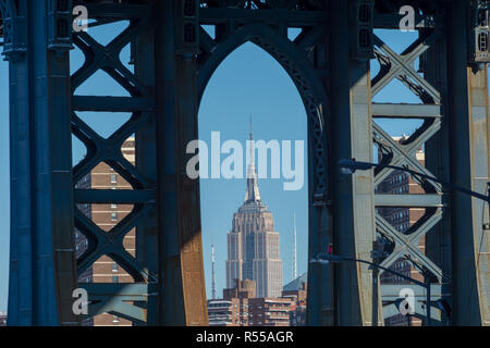 Skyscraper viewed through an arch of the Manhattan Bridge, New York on a clear winter day - Stock Image