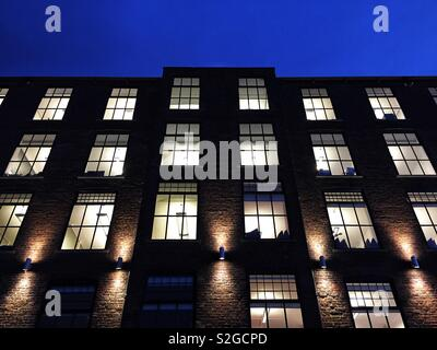 A low angle view of a modern stone building and office block at night with windows illuminated - Stock Image