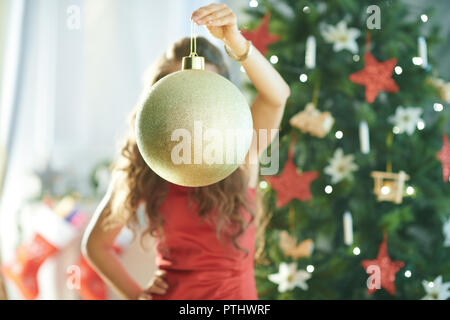 trendy woman in red dress near Christmas tree holding big gold Christmas ball in the front of face - Stock Image