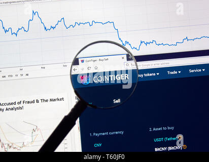 MONTREAL, CANADA - APRIL 26, 2019: Cointiger cryptocurrency digital assets exchange logo and home page on a laptop screen under magnifying glass. - Stock Image