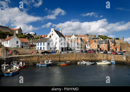 Boats moored at stone pier in Crail Harbour with Crail House lookout turret over the North Sea in Fife Scotland UK - Stock Image