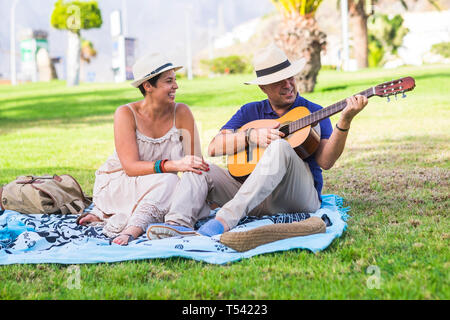 Romantic happy nice caucasian couple people playing a guitar for romantic activity sitting on a meadow in outdoor nature park together - love and rela - Stock Image