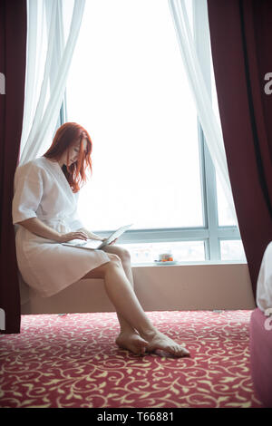 A ginger woman sitting on the window sill - Stock Image