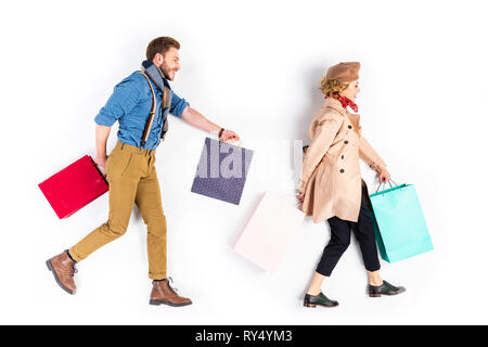Well-dressed couple with shopping bags walking on white background - Stock Image