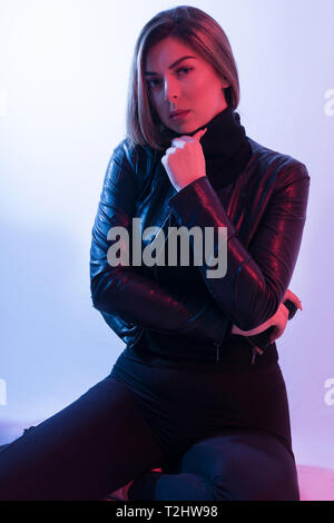 High Fashion model woman in colorful bright lights posing in studio, portrait of beautiful sexy girl with black jacket and red light on face - Stock Image