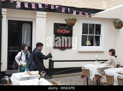 Royal Wedding preparations in Windsor town centre. Tourists photographing each other outside the Prince Harry pub. - Stock Image