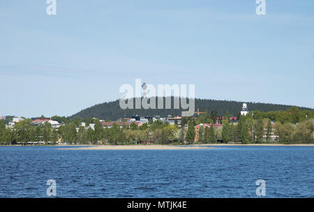 City of Kuopio in Eastern Finland at the shores of Lake Kallavesi, in front of Puijo mountain with its scenery tower and ski-jump tower sticking up. - Stock Image