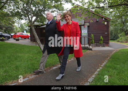 SNP leader Nicola Sturgeon and chief executive of the SNP Peter Murrell leave a polling station at Broomhouse Park Community Hall in Glasgow after casting their votes for the European Parliament elections. - Stock Image