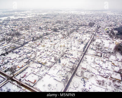 Aerial top view of snowy detached houses in winter - Stock Image