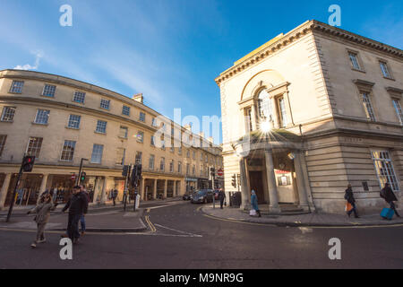 Sunny street scene in Bath at the junction of New Bond Street and Walcot Street with shoppers and cars waiting at traffic lights - Stock Image