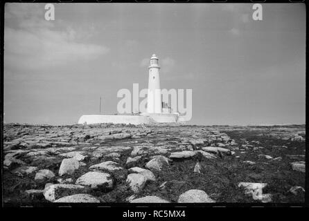 St Mary's Lighthouse, Whitley Bay, North Tyneside, c1955-c1980. An exterior view of the 19th century lighthouse, showing the 126ft tall tower with a partial view of the keeper's cottage to the right, and a stone boundary wall surrounding the complex, seen from the east. The tower of the lighthouse is a white rendered tower 126ft tall, with domes roof and weathervane. The windows are scattered throughout the tower, and the windows of the lantern room at the top have diagonal panes. The keeper's cottage below is a stone building painted white and linked to the tower by a modern single storey ran - Stock Image