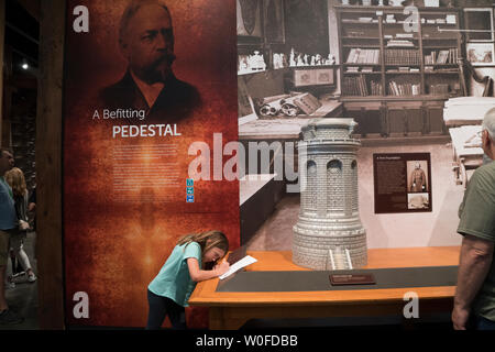 A girl touring the Statue of Liberty Museum on Liberty Island made notes about the statue's pedestal, which was designed by Richard Morris Hunt. - Stock Image