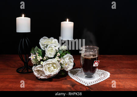 Beautiful bouquet of arranged flowers white candles on a holder, a hot glass of tea on a wooden table. mothers day, Easter, valentines, birthday, Chri - Stock Image