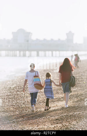 Lesbian couple and daughter holding hands on sunny beach - Stock Image