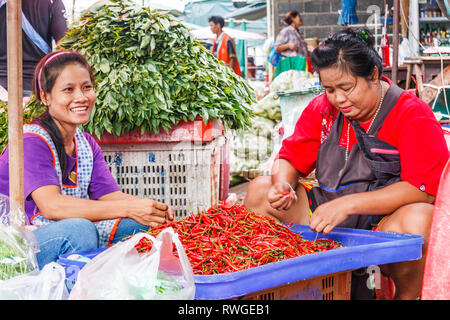 Bangkok, Thailand - 6th September 2009: Vendors sorting chillies on Khlong Toei market. The market is the largest wet market in the city. - Stock Image
