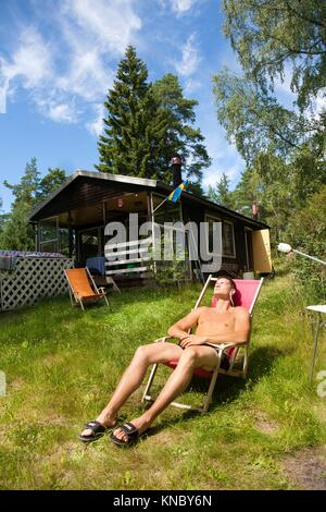 Man sunbathing, Swedish archipelago near Stockholm. - Stock Image