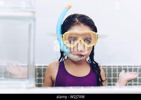 portrait of a funny pretty little girl asking what with snorkel goggles in the tub while taking a bath in the bathtub, kids hygiene concept, copy spac - Stock Image