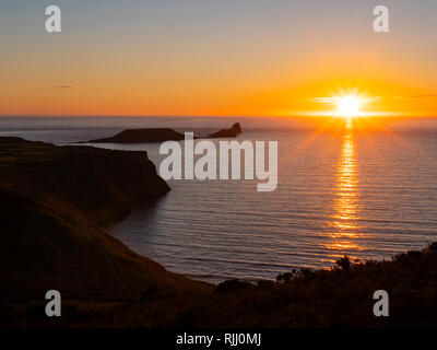 Worms Head Rhossili Gower Swansea Wales in the evening sunset - Stock Image