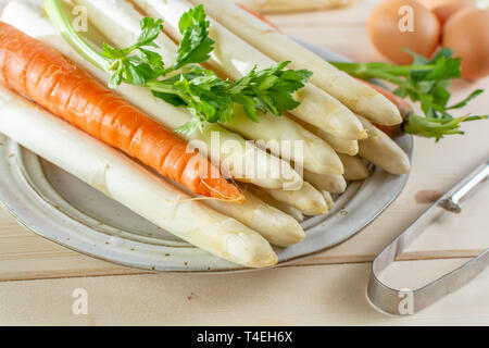 New harvest of white asparagus, high quality raw asparagus, carrot and selery on board in spring season, ready to cook close up - Stock Image