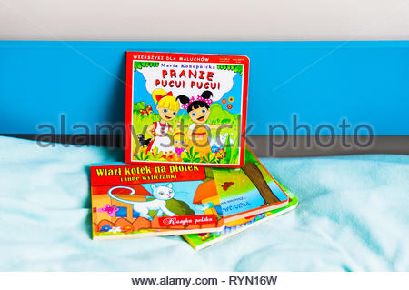 Poznan, Poland - November 18, 2018: Polish colorful book about laundry on a bed. - Stock Image