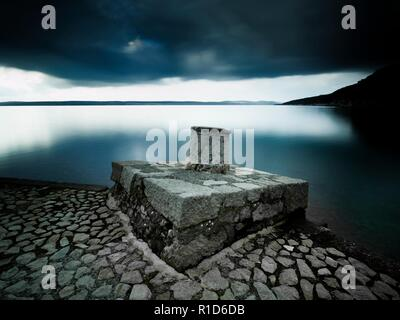 Lonesome bollard on concrete post long exposure Dirakovica Dramalj near Crikvenica in Croatia - Stock Image