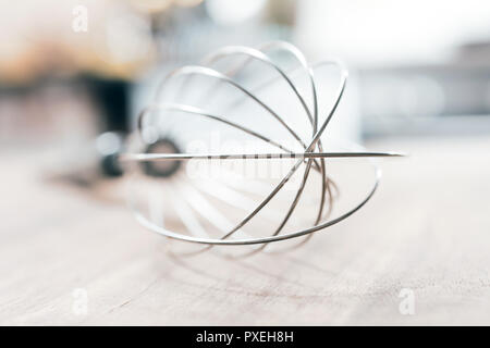 Stainless Whisk On A Wooden Table With Blurred Out Kitchen Background - Stock Image
