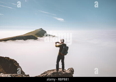 Man traveler taking photo by smartphone in mountains on cliff over clouds Travel blogger vacations lifestyle hobby concept adventure summer trip outdo - Stock Image