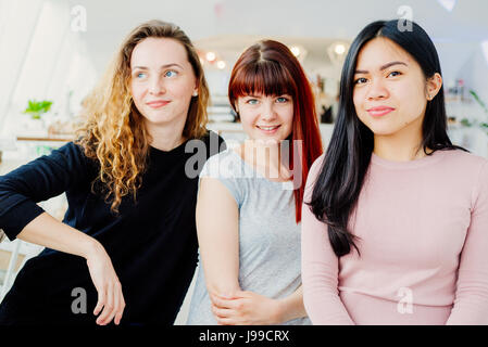 Three young girlfriends posing for a photo - Stock Image