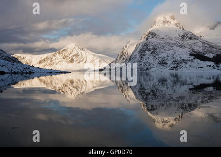 Winter mountain reflections in calm water of Flakstadpollen, Flakstadøy, Lofoten Islands, Norway - Stock Image