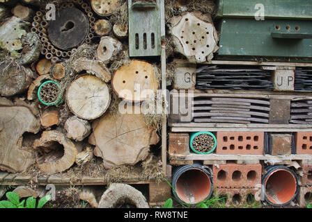 Garden bug hotel made from bricks, slates, cut logs and other re-cycled items, UK - Stock Image