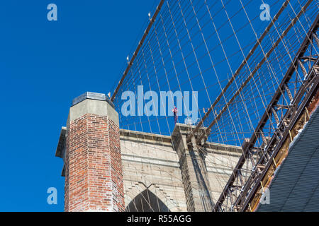 Detail of a tower of the Brooklyn Bridge, new York City with clear blue sky in the background - Stock Image
