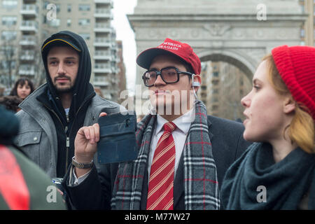 - New York, NY, USA. 8March 2018 Man in a red Make America Great Again hat (MAGA) records activists durig a rally - Stock Image