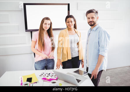 Portrait of confident editors in meeting room at creative office - Stock Image