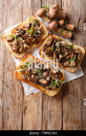 Sandwiches with fried porcini mushrooms, caramelized onions and thyme close-up on the table. Vertical top view from above - Stock Image