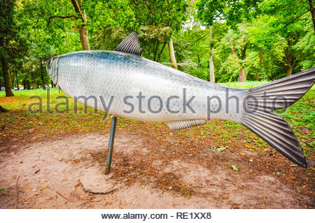 Kolobrzeg, Poland - August 10, 2018: Large herring model by a park with trees - Stock Image