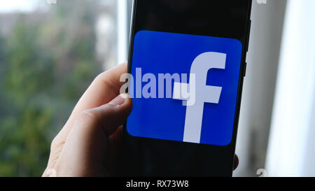 hand and finger use facebook app symbol on a smartphone - Stock Image