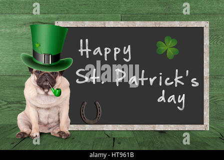 cute pug puppy dog with leprechaun hat for st. patrick's day smoking pipe, sitting next blank chalkboard sign - Stock Image