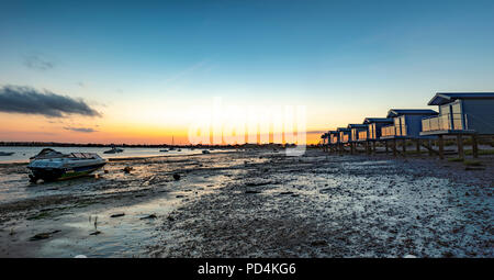 Osea minimalist Beach huts in England modelled on huts in Maldives captured at sunset in summer on secluded beach at low tide Blackwater Estuary - Stock Image