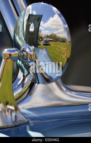 Floral Park, New York, U.S. 27th April, 2014. The 1961 Chevrolet Corvette convertible rear view mirror reflects a beautiful blue sky over the field at the 35th Annual Antique Auto Show at Queens Farm. Credit:  Ann E Parry/Alamy Live News - Stock Image