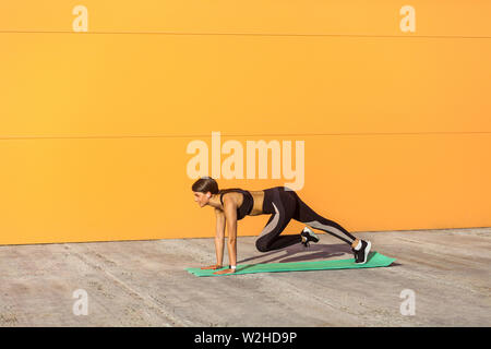 Young beautiful fitness girl in black sportwear on summer street doing abs exercise to tone stomach muscles. Woman training outdoors on exercise mat. - Stock Image