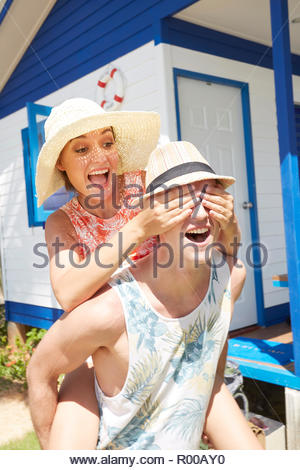 Young man piggybacking young woman while his eyes are covered - Stock Image
