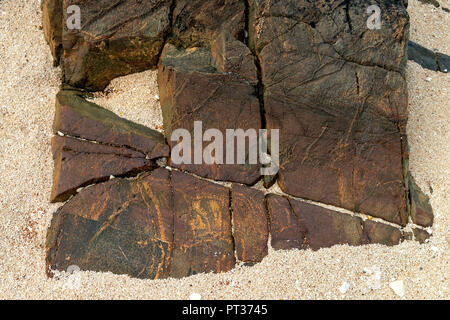 A Red geometrical stone formation on a beach, made up with broken triangles , square, rectangles,  missing one piece, and containing straight lines. - Stock Image