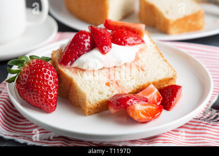 Portion of angel food cake served with whipped cream and strawberries - Stock Image