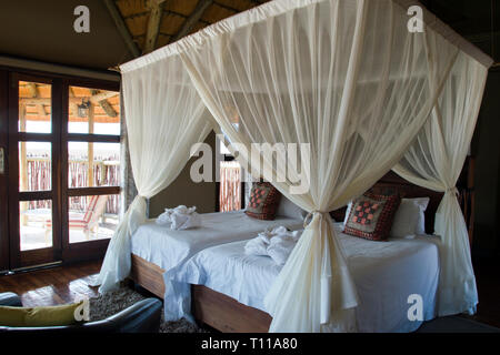 Mosquito nets cover the bed in a luxury rondavel (chalet) at a desert lodge near the famous red sand-dunes of Sossusvlei inside the Namib-Naukluft Par - Stock Image