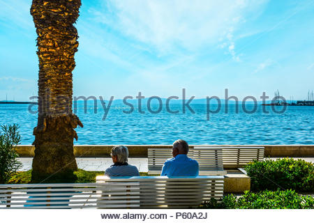 An older couple relax on a bench on the Riva waterfront promenade, on the Dalmatian coast of Split, Croatia - Stock Image