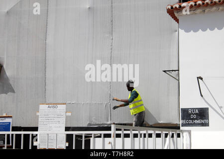 Man working outside on building with protective cove undergoing renovation in the Alfama quarter of Lisbon Portugal Europe EU  KATHY DEWITT - Stock Image