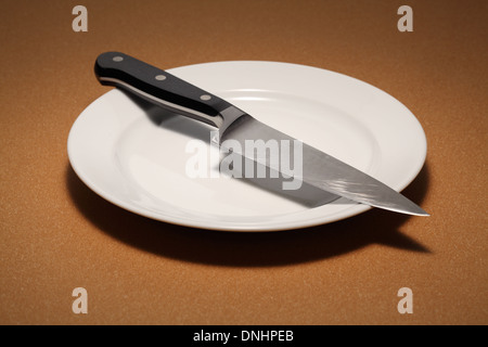 A large kitchen chef's knife on a empty white dinning plate. - Stock Image