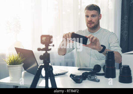 social media technology vlogger doing smart phone review in front of camera - Stock Image