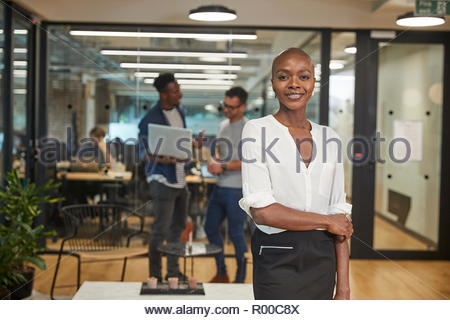 Smiling young businesswoman in office - Stock Image